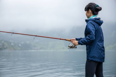 Woman fishing on Fishing rod spinning in Norway. 写真素材 - 128819926