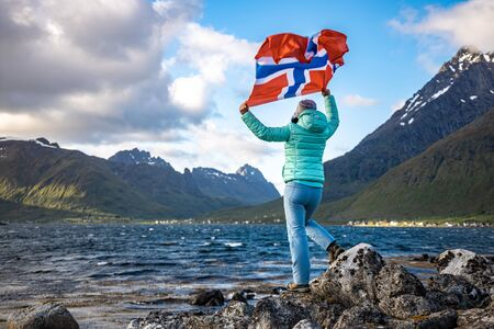 Woman with a waving flag of Norway of nature 写真素材 - 128819936