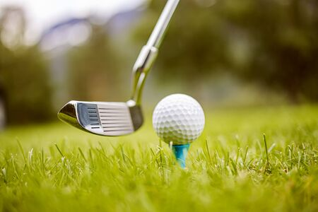 Golf club and ball on tee in front of driver 写真素材