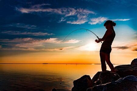 Woman fishing on Fishing rod spinning in Norway. 写真素材 - 128820713