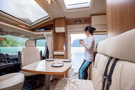 Woman in the interior of a camper RV motorhome with a cup of coffee looking at nature. 写真素材 - 128820701