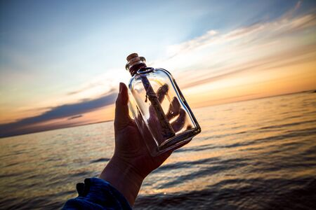 Message in the bottle against the Sun setting down 写真素材 - 128820711