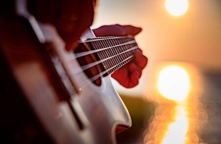 Woman at sunset playing the ukulele 写真素材