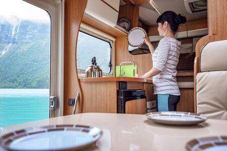 Woman cooking in camper, motorhome RV interior.