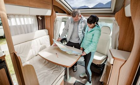 Couples in RV Camper looking at the local map for the trip. Stock Photo - 128820756