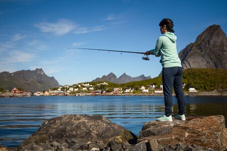 Woman fishing on Fishing rod spinning in Norway. 写真素材 - 128820755