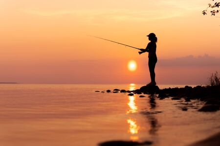 Woman fishing on Fishing rod spinning in Norway. 写真素材 - 128820284