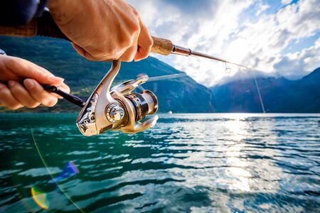 Woman fishing on Fishing rod spinning in Norway. 写真素材 - 128820291