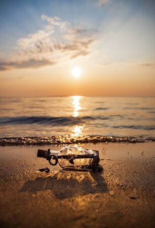 Message in the bottle against the Sun setting down 写真素材 - 128820280