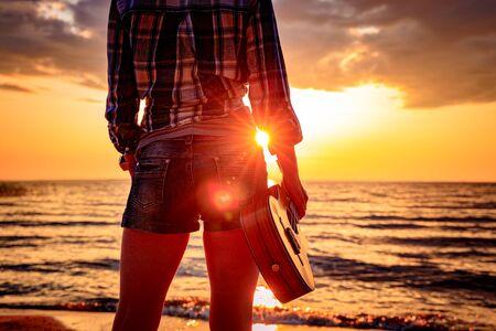 Woman at sunset holding a ukulele 写真素材 - 128820287