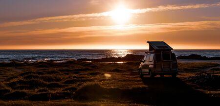 Camping car minivan on the beach at sunset. 写真素材