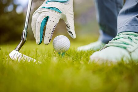 Hand in glove placing golf ball on tee 写真素材 - 128820331
