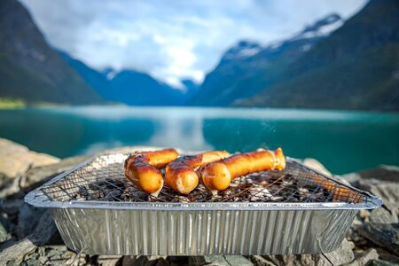 Grilling sausages on disposable barbecue grid.
