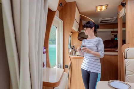 Woman in the interior of a camper RV motor home with a cup of coffee looking at nature. 写真素材 - 130315951