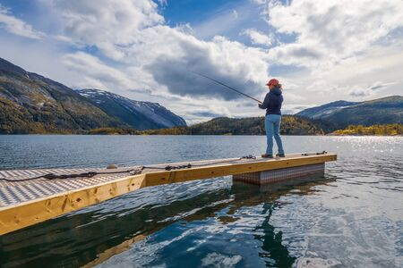 Woman fishing on Fishing rod spinning in Norway. 写真素材 - 130315999
