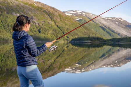 Woman fishing on Fishing rod spinning in Norway. Fishing in Norway is a way to embrace the local lifestyle. 写真素材 - 130316003