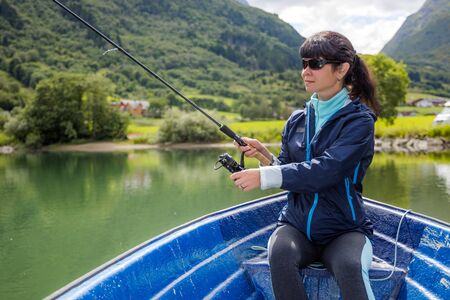 Woman fishing on Fishing rod spinning in Norway. 写真素材 - 130316090