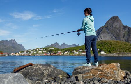 Woman fishing on Fishing rod spinning in Norway. Fishing in Norway is a way to embrace the local lifestyle. 写真素材