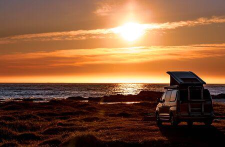 Camping car minivan on the beach at sunset. Beautiful Nature Norway natural landscape Lofoten beach.