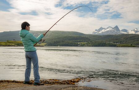 Woman fishing on Fishing rod spinning in Norway. Fishing in Norway is a way to embrace the local lifestyle. Countless lakes and rivers and an extensive coastline means outstanding opportunities... 写真素材 - 131393564