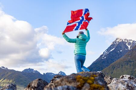 Woman with a waving flag of Norway on the background of nature Stock fotó
