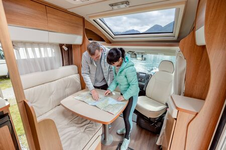 Couples in RV Camper looking at the local map for the trip. Family vacation travel, holiday trip in motorhome, Caravan car Vacation. Stockfoto
