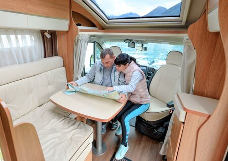 Couples in RV Camper looking at the local map for the trip. Family vacation travel, holiday trip in motorhome, Caravan car Vacation. Stok Fotoğraf