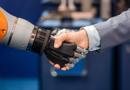 Hand of a businessman shaking hands with a  robot.