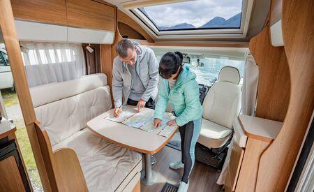 Couples en camping-car en regardant la carte locale pour le voyage. Voyage de vacances en famille, voyage de vacances en camping-car, vacances en voiture caravane.