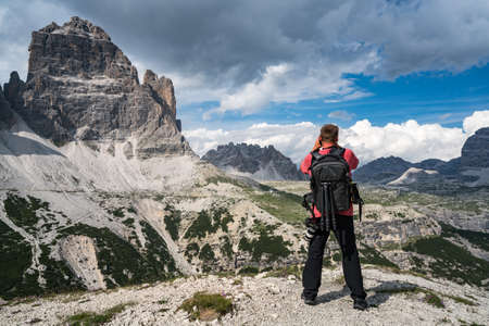Nature photographer tourist with camera shoots while standing Italy Dolomites Alps. 写真素材