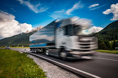 Fuel truck rushes down the highway in the background the Alps. Truck Car in motion blur. 写真素材