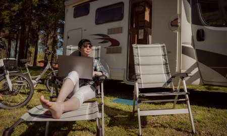 Woman looking at the laptop near the camping . Caravan car Vacation. Family vacation travel, holiday trip in motorhome RV. Wi-fi connection information communication technology. 写真素材