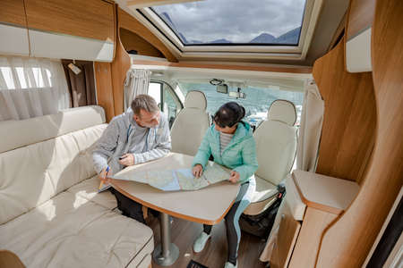 Couples in RV Camper looking at the local map for the trip. Family vacation travel, holiday trip in motorhome, Caravan car Vacation. 写真素材