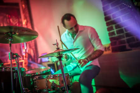Drummer playing on drum set on stage. Authentic shooting with high iso in challenging lighting conditions. A little bit grain and blurred motion effects.