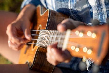 Woman at sunset playing the ukulele Standard-Bild
