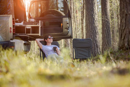 Trip in the nature by car family vacation on the weekend. Woman traveller enjoy coffee time.