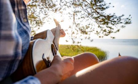 Woman at sunset playing the ukulele Foto de archivo