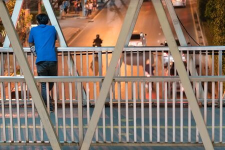 Man standing alone on the bridge. Asian man standing behind and holding a beer can on the footbridge and looking at the car run on the street, in the city night time.