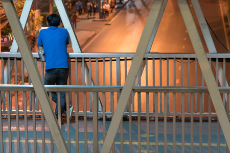 Asian man standing behind and holding a beer can on the footbridge and looking at the empty street not running cars, This is night time in the city of Bangkok. Banco de Imagens