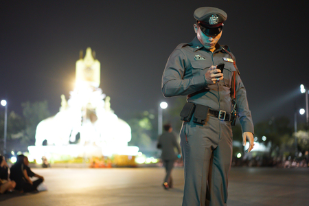 Thailand police are using smartphones in a ceremony to worship King Rama 9. He is checking the information for protecting people In the night of Bangkok.