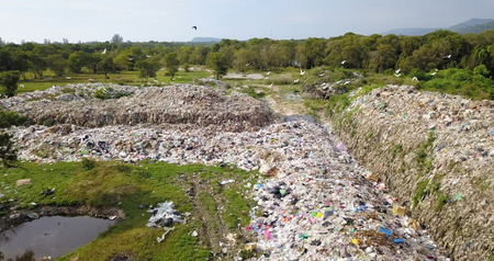 Birds eye view of garbage mountain from drone in the industrial zone. Here is a flock of white birds, living in the garbage dump hill, The flock live in the forest near the garbage zone. this is a very serious risk of pollution.