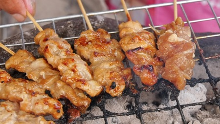 Thai style BBQ pork fat are grilled on the  aluminium grid with wood charcoal  that some are burnt to grate. It is the most popular street food for Thai people especially  in the morning time. Banco de Imagens