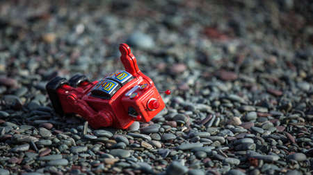defeated: Knocked over by a rogue wave, the red robot is down, but not defeated. A vintage tin toy laying on a rocky beach after being hit by an ocean wave.