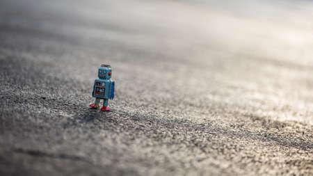 블루 팔과 빨간 발을 포장에 빈티지 회색 깡통 로봇 산책입니다. 게다가 그것의 머리에 코일.