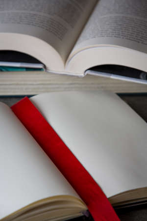 Multiple open books on table, one marked with a red ribbon