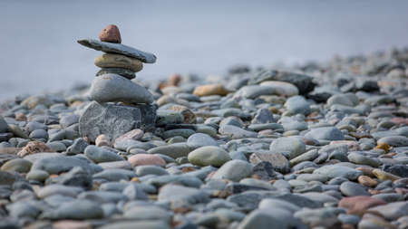 inukshuk: Small inukshuk on a rocky beach next to the ocean
