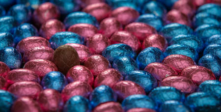 foil: One unwrapped chocolate egg, surrounded by foil wrapped eggs Stock Photo