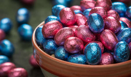 foil: Bowl filled with ping and blue foil wrapped chocolate easter eggs.
