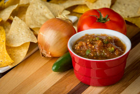 corn chips: Fresh tomato salsa surrounded by ripe tomatoes and jalapenos. In the background is corn chips.