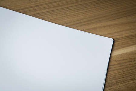 looseleaf: Blank sheets of white paper on wooden desk, ready for artwork.